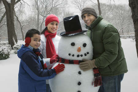 Hispanic family making snowman