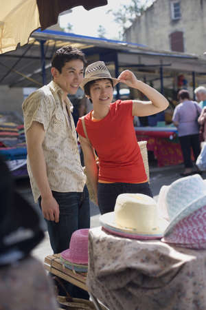 shopping buddies: Asian couple trying on hats at market
