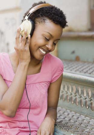 stoop: African woman listening to headphones outdoors