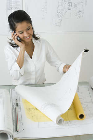 asian architect: Female Asian architect working at desk LANG_EVOIMAGES