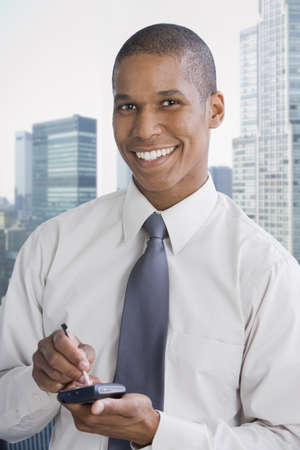 electronic organizer: Mixed race businessman using electronic organizer LANG_EVOIMAGES