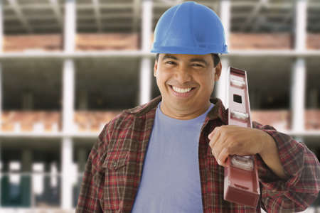 Hispanic construction worker holding level Stock Photo