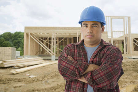 conferring: Hispanic construction worker at construction site LANG_EVOIMAGES