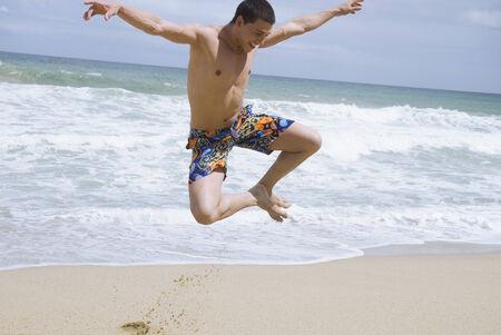Hispanic man at beach jumping in mid-air Stok Fotoğraf