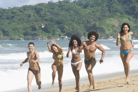Multi-ethnic friends running on beach 스톡 콘텐츠