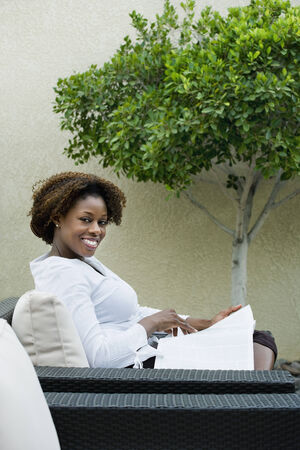 casualness: African woman reading on patio LANG_EVOIMAGES