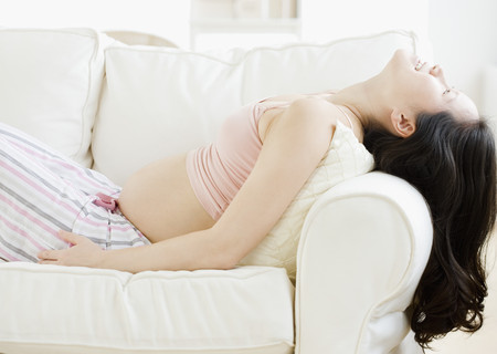 asian pregnant: Pregnant Asian woman reclining on sofa