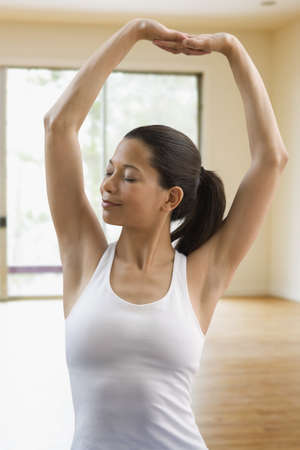 chinese american ethnicity: Mixed race woman doing yoga LANG_EVOIMAGES
