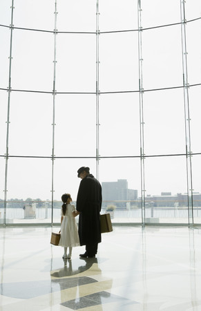 Hispanic father and daughter waiting in airport Stock Photo
