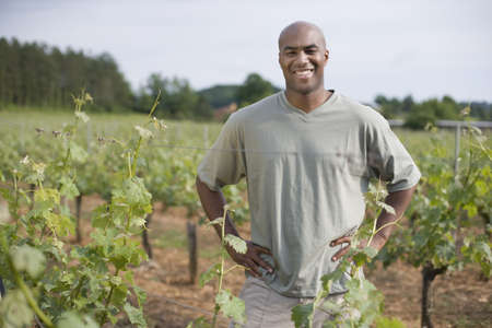 one mid adult male: African man standing in vineyard LANG_EVOIMAGES