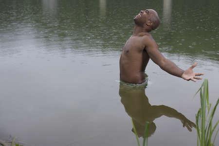 tugging: Shirtless African man wading in lake