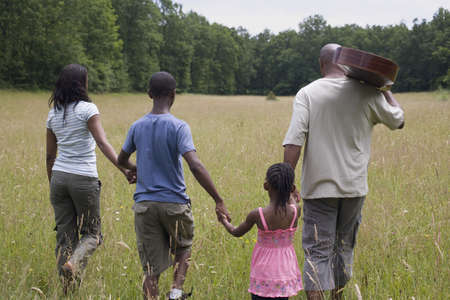 poppa: African family holding hands in field