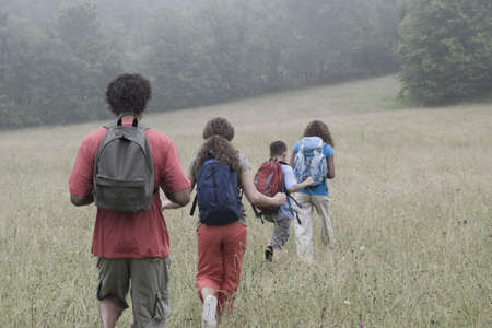 Mixed race family hiking with backpacks Stock Photo