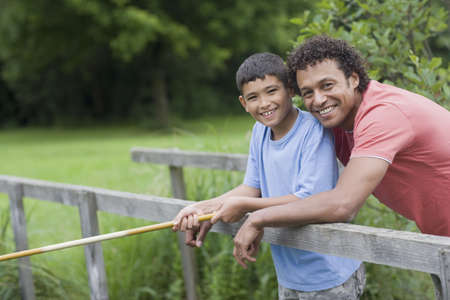 midsummer pole: Mixed race father and son fishing on bridge LANG_EVOIMAGES