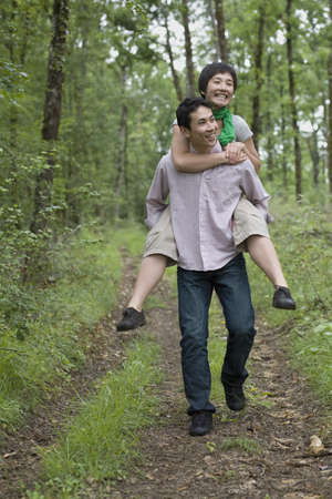 mischievious: Asian man giving girlfriend piggy back ride in forest