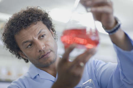 shrieking: Mixed race scientist working in laboratory with beaker of liquid LANG_EVOIMAGES