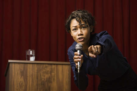 Mixed race businesswoman speaking on stage and pointing Stock Photo