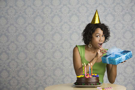 Surprised mixed race woman with birthday cake and gift Stock Photo