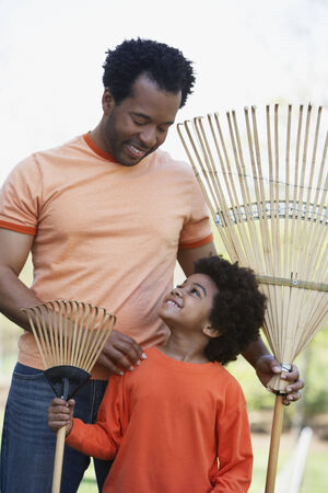 African father and son holding rakes Stock Photo