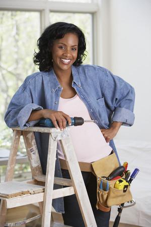 Afrikaanse vrouw met boor en toolbelt Stockfoto