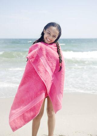 bathtowel: Wet Hispanic girl wrapped in towel on beach