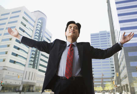lecturing: Chinese businessman on city street with arms outstretched