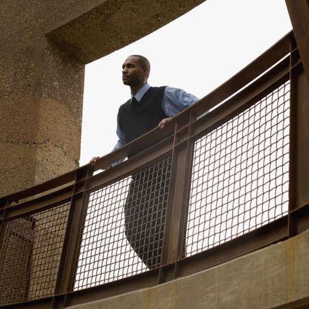 resolving: Uomo d'affari africani in piedi sul balcone LANG_EVOIMAGES