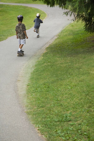 generation gap: Asian boys skateboarding downhill