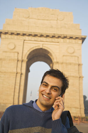 india gate: Indian man talking on cell phone near the India Gate LANG_EVOIMAGES