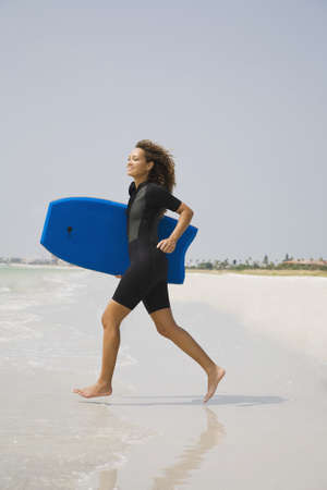 jamaican ethnicity: Mixed race woman running with boogie board at beach