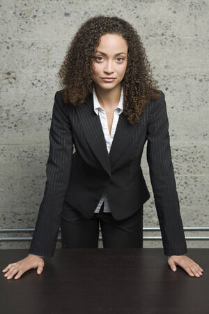 mischievious: Confident African businesswoman leaning on table