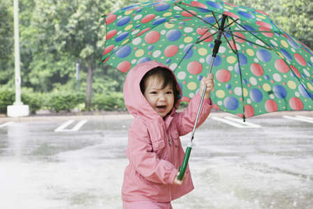 living being: Mixed race girl holding umbrella