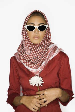 middle eastern woman: Middle Eastern woman in burkha holding flower LANG_EVOIMAGES