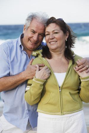 Hispanic couple hugging on beach 스톡 콘텐츠