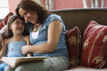 generation gap: Hispanic grandmother reading to granddaughter