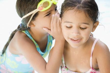 dunce cap: Hispanic girl whispering to sister