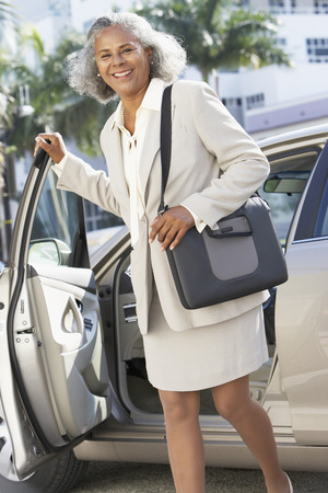 African businesswoman standing next to car
