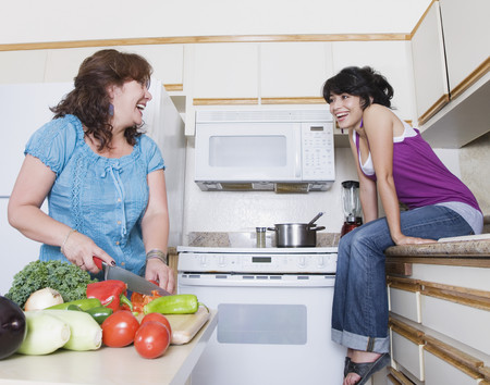 Mother preparing meal and talking to daughter