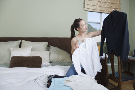separating: Woman packing clothes for business trip