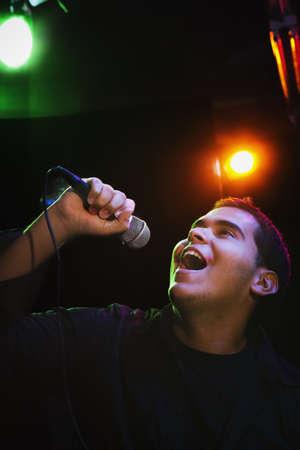 nite: Hispanic man singing in nightclub LANG_EVOIMAGES