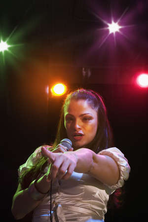 seriousness skill: Hispanic woman singing in nightclub