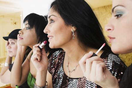 nite: Hispanic woman applying makeup in bathroom LANG_EVOIMAGES
