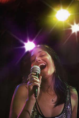 nite: Hispanic woman singing in nightclub