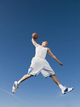 アフリカの男が空中でバスケット ボールをプレー