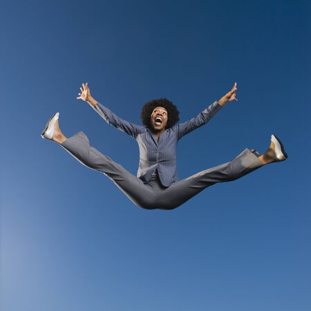 flexible: African businesswoman jumping in mid-air