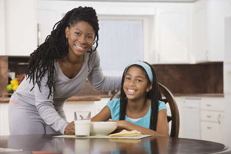 African girl eating breakfast in kitchen with mother