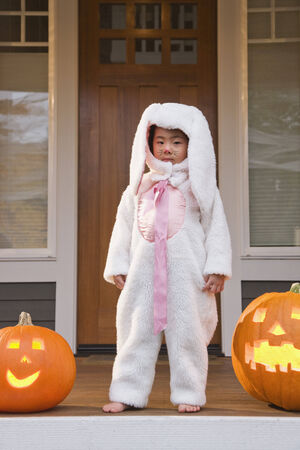 full length herbivore: Young Chinese girl in rabbit costume with Halloween pumpkins