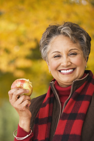 African woman eating apple outdoors in autumn