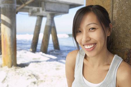 Asian woman smiling near pier at beach Banco de Imagens