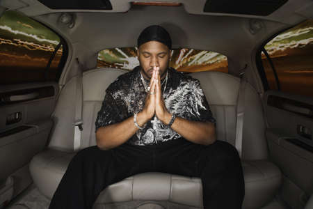 African man praying in back seat of car